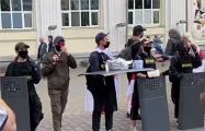 Протестующие в форме ОМОН предлагают людям драники